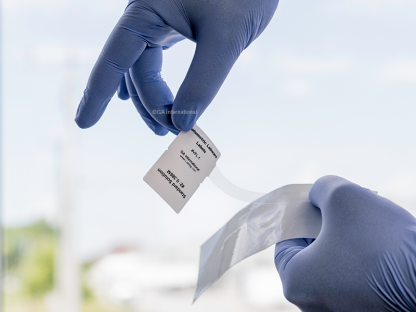 A gloved hand peeling a thermal transfer volumetric labware label from its liner. Label is printed with alphanumeric text.