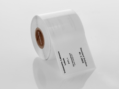 A roll of thermal-transfer volumetric labware labels, printed with standard information, on a lab table.