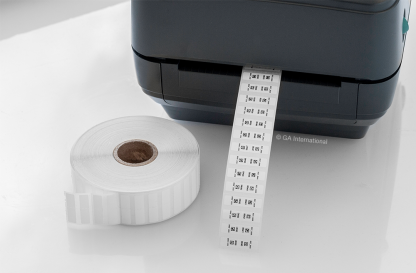 A thermal-transfer printer printing chemical resistant labels for resin-embedding, next to a blank roll of ResiTAG labels, on a lab table.