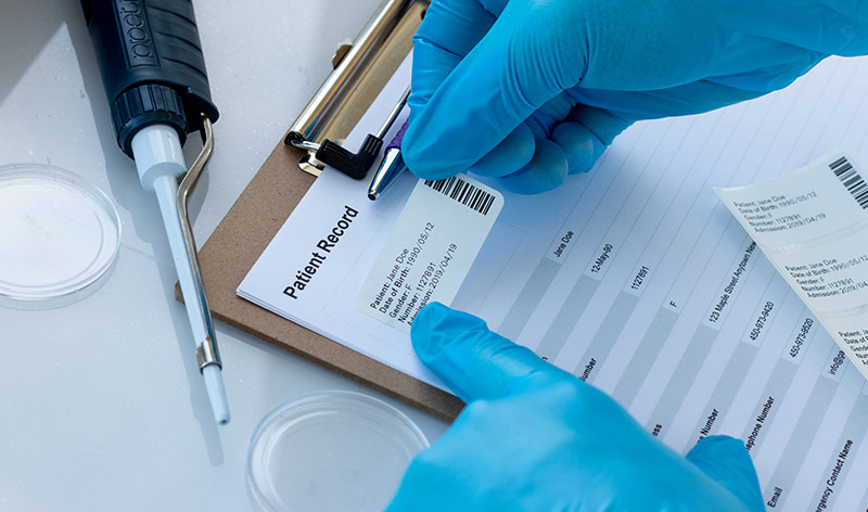 A gloved hand applying a thermal-transfer paper datasheet label on a patient record form. The white label is printed with patient info and a barcode.