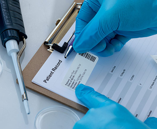 A gloved hand applying a general use thermal-transfer paper label to a patient record form. Label is printed with patient info and a 1D barcode.