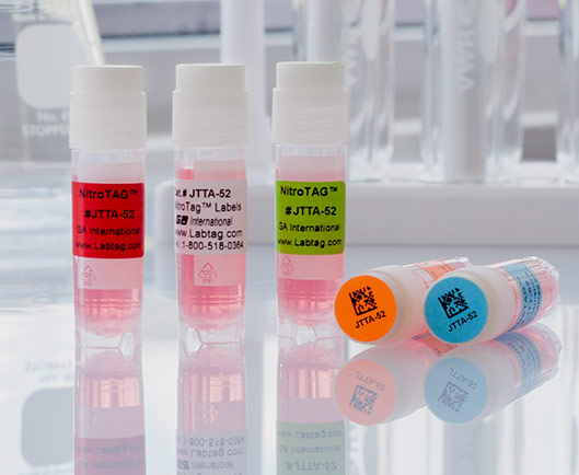 Three standing cryo vials, along with two lying down. Vials are labeled with color barcode printed cryogenic thermal-transfer labels and dots.